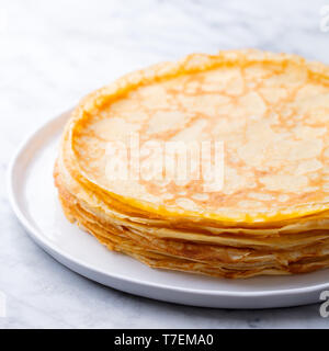 Crepes, thin pancakes, blini on a white plate. Marble background. Close up. - Stock Photo