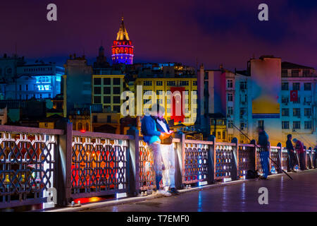 Two unrecognisable men using smartphone in front of Galata tower and colorful buildings of Karakoy seen from Galata Bridge at night. Istanbul, Turkey. - Stock Photo