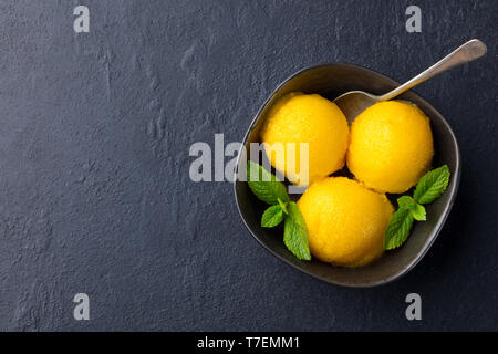Mango ice cream, tropical fruit sorbet in black bowl on slate background. Copy space. Top view. - Stock Photo