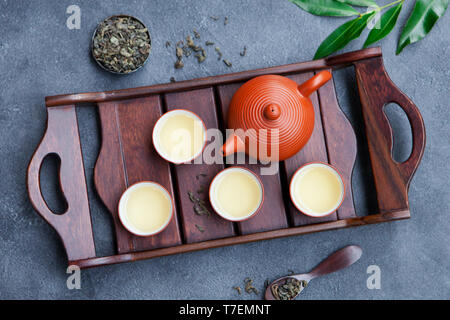 Green tea in tea pot and bowls, cups on slate background. Top view. - Stock Photo