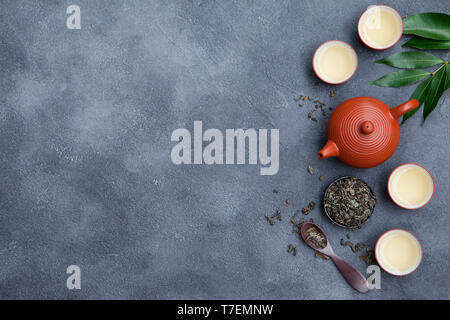 Green tea in tea pot and chawan bowls, cups on slate background. Top view. Copy space. - Stock Photo