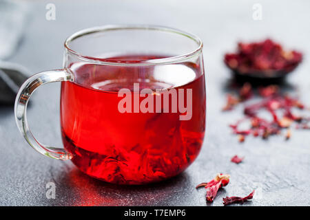 Hibiscus tea in glass cup. Grey background. Close up. - Stock Photo