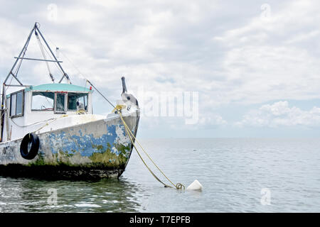 Pelican sitting on old SHIP IN SEA AGAINST SKY - Stock Photo