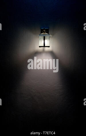 Square glass lamp LED beam light on the white wall in the dark. - Stock Photo