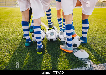 Group of young football players on soccer training. Legs of soccer kids kicking balls on field. Summer sunset in the background. Football training bac - Stock Photo