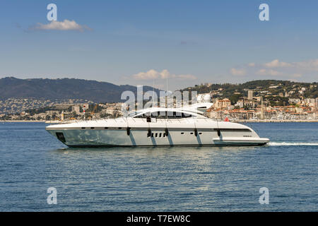 CANNES, FRANCE - APRIL 2019: Luxury motor yacht cruising in the bay in Cannes with the beach and seafront buildings in the background. - Stock Photo