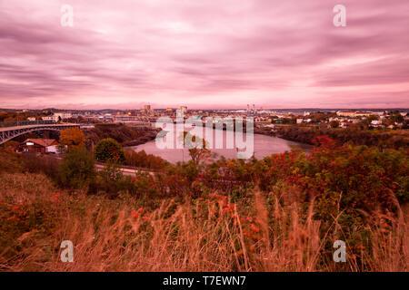 The Saint John River and many trees during autumn at sunset in Saint John, New Brunswick, Canada. - Stock Photo