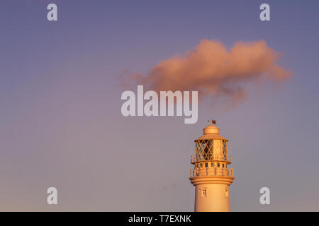 View of Flamborough lighthouse at sunset with a single cloud travelling over the top in blue sky and pink light of the setting sun, East Yorkshire, UK - Stock Photo