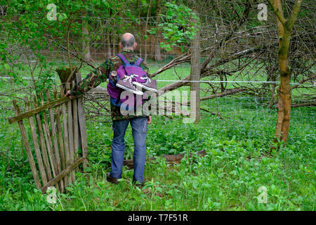 older man backpacking in countryside standing by old wooden gate and confronted by anti deer and electric fences blocking his way zala county hungary - Stock Photo