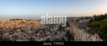 Beautiful aerial panoramic view of the Walls of Jerusalem surrounding the Old City with the cityscape in the background during a sunny sunset. Taken n - Stock Photo