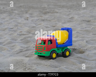 colorful truck cement (concrete) mixer plastic toy on the sand dunes - Stock Photo