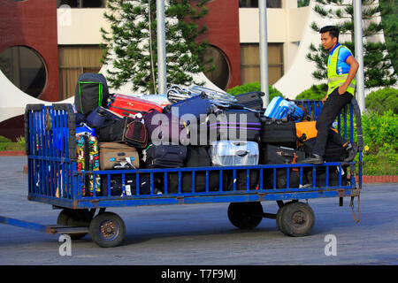 Baggage handler moving luggage at airport airside Hazrat Shahjalal Hazrat Shahjalal International Airport in Dhaka, Bangladesh. - Stock Photo