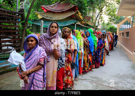 Poor Muslim women wait in a queue if front of the Dharmarajik Buddhist Vihara in Dhaka for iftar (food for fasting).  Monks at Dharmarajik Buddhist Vi - Stock Photo