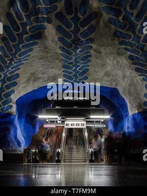 Blue pattern ceiling subway station and people moving through escalators in Stockholm, Sweden - Stock Photo