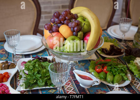 Red and blue apple, orange, red banana banana. Cucumber, tomato, greens, radish. Fruit in a bowl . - Stock Photo