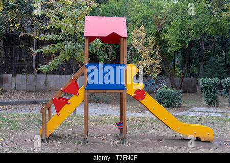 Colorful children playground on yard activities in public park surrounded by green trees. Urban neighborhood childhood concept. - Stock Photo