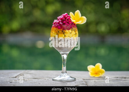 Chia seeds pudding with red dragon fruit, passion fruit, mango and avocado in a glass for breakfast on the background of the swimming pool water, clos - Stock Photo