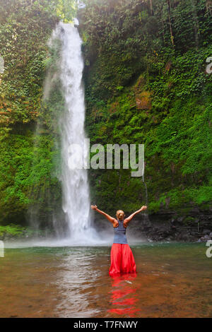 Young woman travel in Bali rainforest. Happy girl enjoy jungle nature. Stand in natural pool under waterfall, see on falling water. Walking day tour - Stock Photo