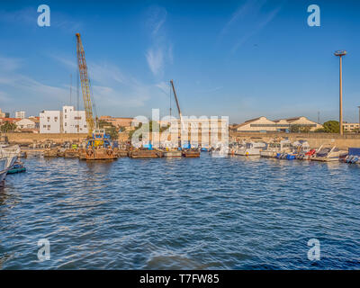 Dakar, Senegal - February 2, 2019: View of the port of Dakar in Senegal with big ships, small boats, cranes and cargos near the quay. Africa. - Stock Photo