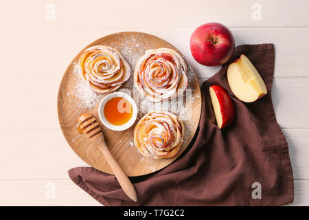 Tasty rose shaped apple pastry and honey on wooden tray - Stock Photo