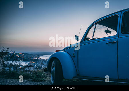 vintage beetle car at sunset, to make a road trip millennial - Stock Photo
