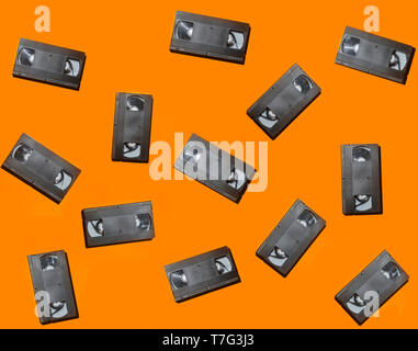 Creative background from video cassettes on an orange surface. Top view. - Stock Photo
