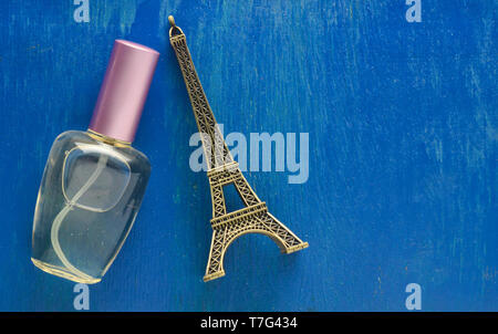 A perfume bottle and a souvenir statuette of the Eiffel Tower on a blue background. - Stock Photo