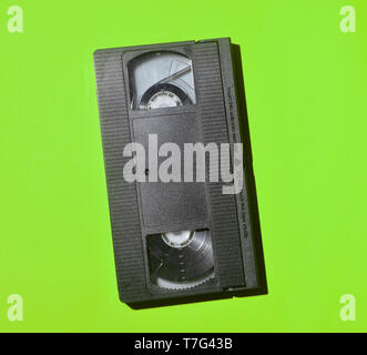 Retro videocassette from 80s on a green background. Obsolete media technologies. - Stock Photo