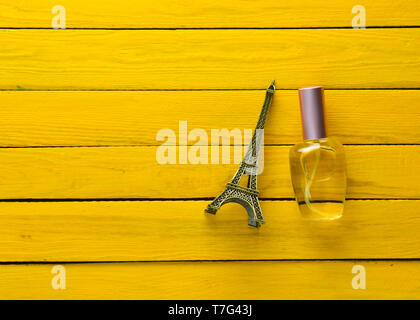 A perfume bottle and a souvenir statuette of the Eiffel Tower on a yellow wooden background. - Stock Photo