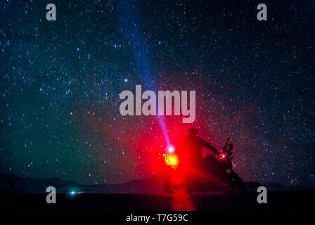 Biker under stars in winter spiti - himalayas in india - Stock Photo