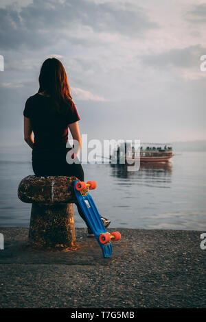 relax woman sit in front of the sea with her skateboard and looking into infinite - Stock Photo