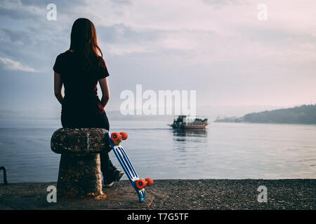Chill woman sit in front of the sea with her skateboard and looking into infinite - Stock Photo