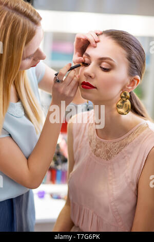 Attractive young woman having a professional makeup - Stock Photo