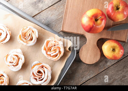 Baking tray with tasty rose shaped apple pastry on wooden table - Stock Photo