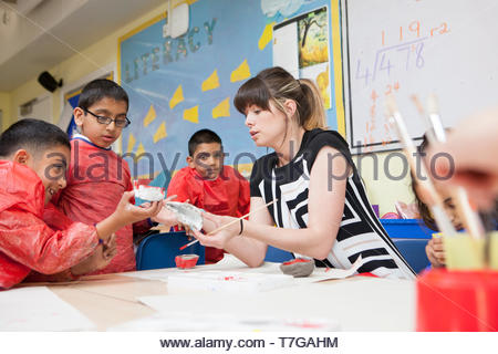 An NQT works with her primary school children in an art class UK - Stock Photo