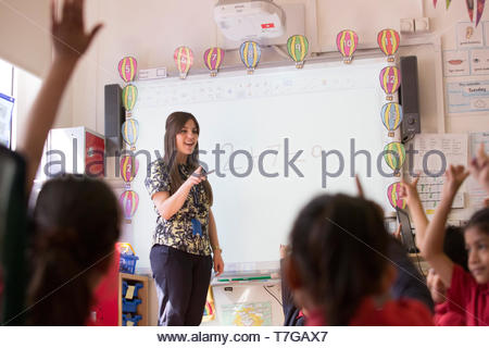A young female maths teacher looks for help from her class in solving a problem fro the white board UK - Stock Photo