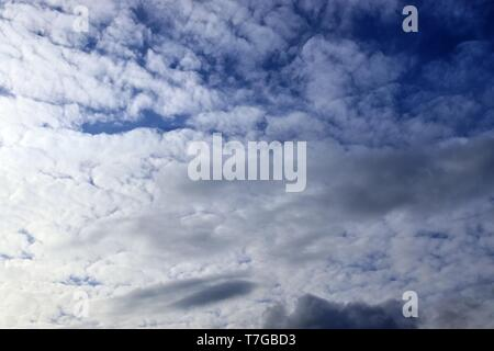Interesting white and dark mixed cloud formations on a blue sky in spring - Stock Photo