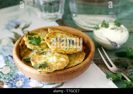 Pancakes with zucchini and sweet corn, served with sour cream, parsley and dill. Vegetarian food, selective focus. - Stock Photo