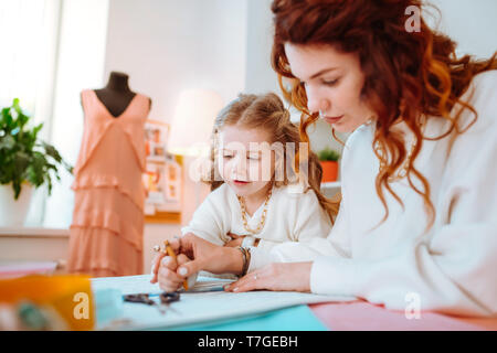 Appealing cute girl standing near mother designing dresses - Stock Photo