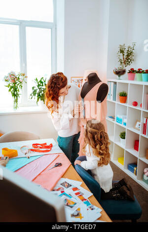 Designer standing near dress form with her little daughter - Stock Photo