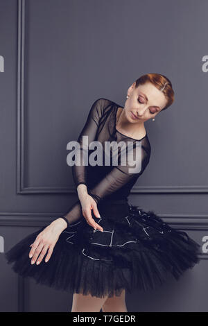 Ballerina in a black tutu posing on a black background. - Stock Photo