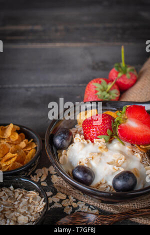 Yoghurt mix oatmeal, strawberry and grape topping in black bowl on sack and wood table with spoon, oatmeal, cornflakes and strawberry placed around. - Stock Photo