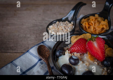 Yoghurt mix oatmeal, strawberry and grape topping in black bowl on Blue and white striped fabric and wood table with spoon, cornflakes and oatmeal pla - Stock Photo