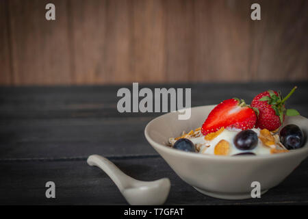 Yoghurt mix oatmeal, strawberry and grape topping in white bowl on the wood table with spoon placed beside - Stock Photo