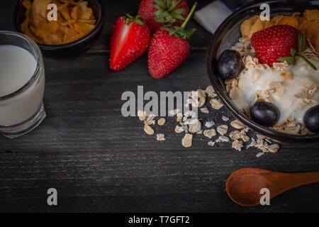 Yoghurt mix oatmeal, strawberry and grape topping in black bowl on wood table with spoon, strawberry, milk in glass, cornflakes and oatmeal placed aro - Stock Photo