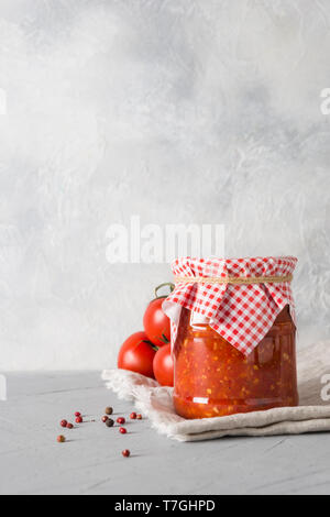 Homemade vegetable traditional Maghrebi adjika with hot chili pepper sauce and tomatoes in jar on light background. Paste harissa. Tunisia and Arabic  - Stock Photo
