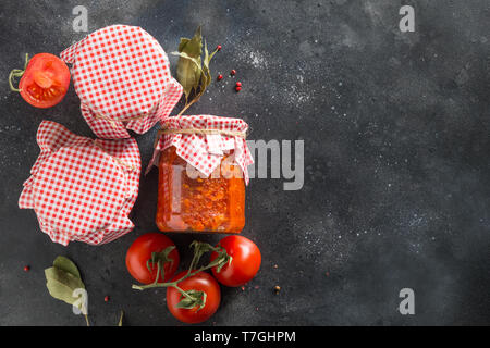 Homemade adjika in jar on black background. Made of tomatoes, garlic, bell pepper and spice. View from above. Tunisia and Arabic cuisine adjika. Regio - Stock Photo