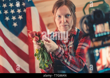 Female farmer making social media vlog video about farm work and seasonal agricultural activity, woman dressed as farm worker in front of the camera t - Stock Photo