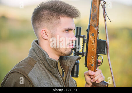 Hunting masculine hobby concept. Man brutal gamekeeper nature background. Regulation of hunting. Hunter hold rifle. Bearded hunter spend leisure hunting. Focus and concentration of experienced hunter. - Stock Photo