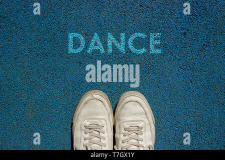 New life concept, Sport shoes and the word DANCE written on blue walk way ground, Motivational Slogan. - Stock Photo